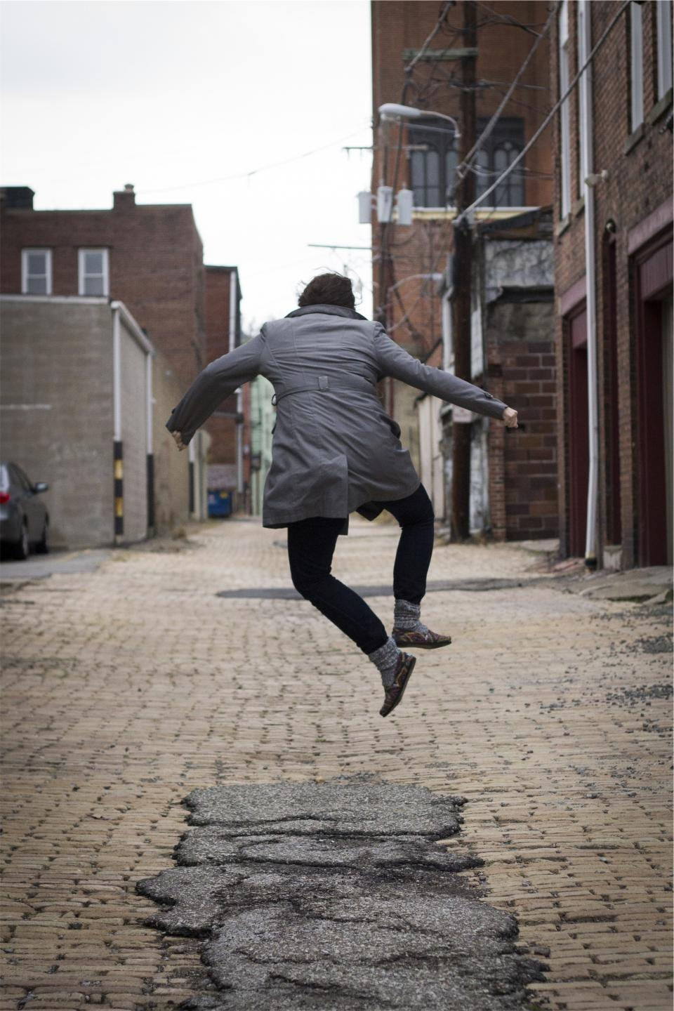 girl, jumping, happy, people, woman, jacket, pants, socks, shoes, cobblestone, alley, pavement