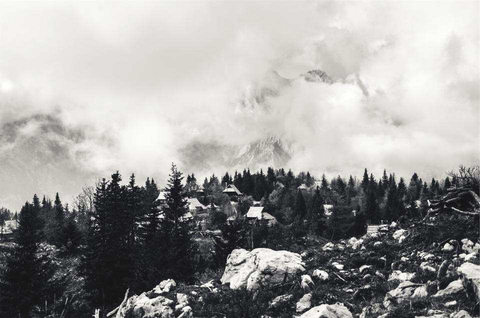 landscape, houses, rocks, boulders, trees, mountains, clouds, black and white
