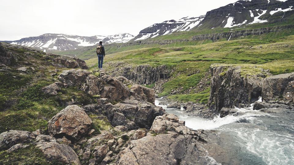 mountains, cliffs, valleys, fields, snow, rocks, water, stream, nature, outdoors, hike, trek, trail, hiker, man, backback, knapsack, backpack, green, grass