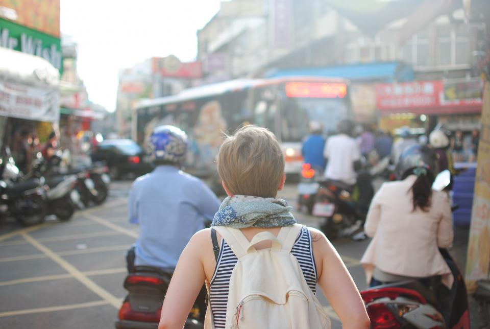 girl, woman, bag, knapsack, backpack, scooter, motorbike, helmet, bus, city, town, street, road, people, traffic, busy, shops, tores, buildings, scarf