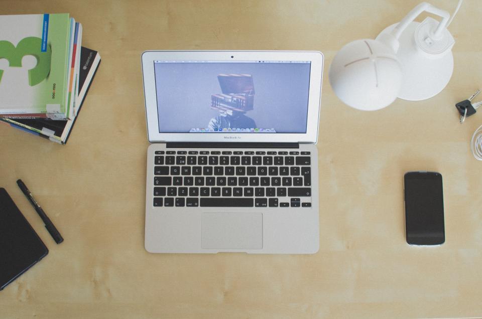wood, desk, work, laptop, macbook air, iphone, lamp, light, pen, textbook, note book, screen, technology, office, business