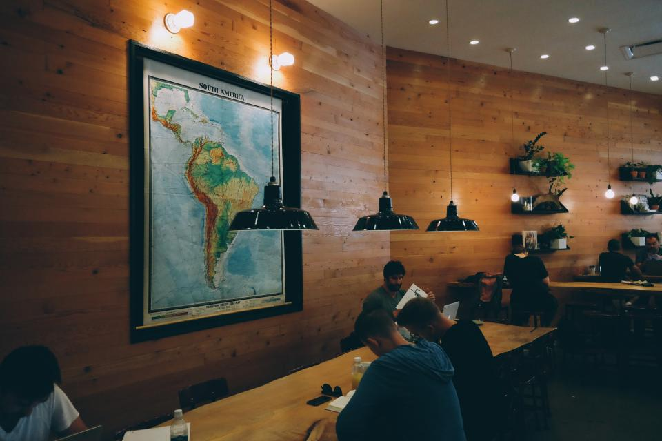 group, people, reading, working, cafe, restaurant, coworking, lights, wood, tables, map