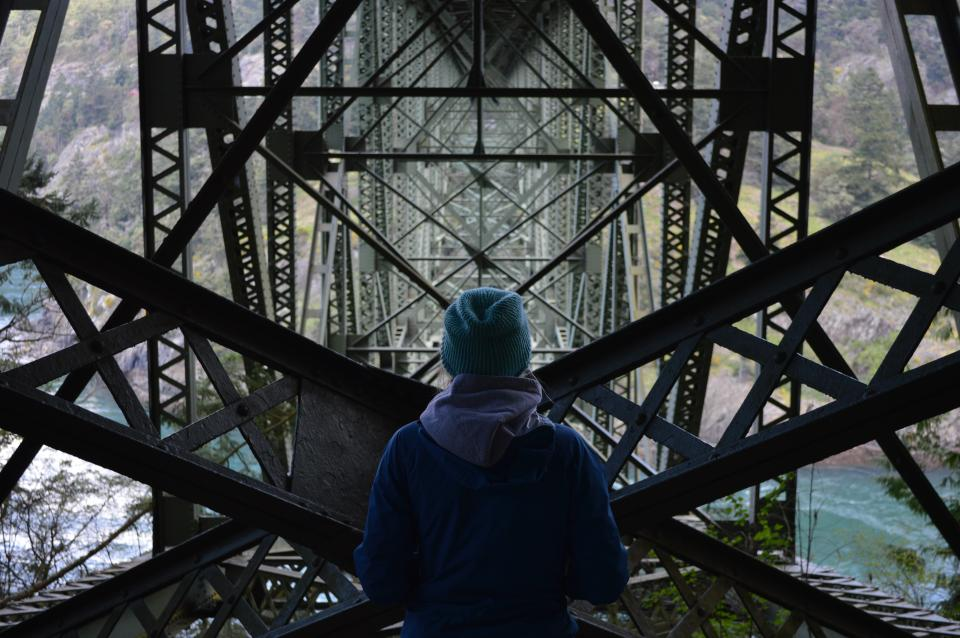 guy, man, male, people, back, contemplate, stand, nature, landscape, mountains, trees, grass, water, waves, river, bridge, structures, steel, industrial