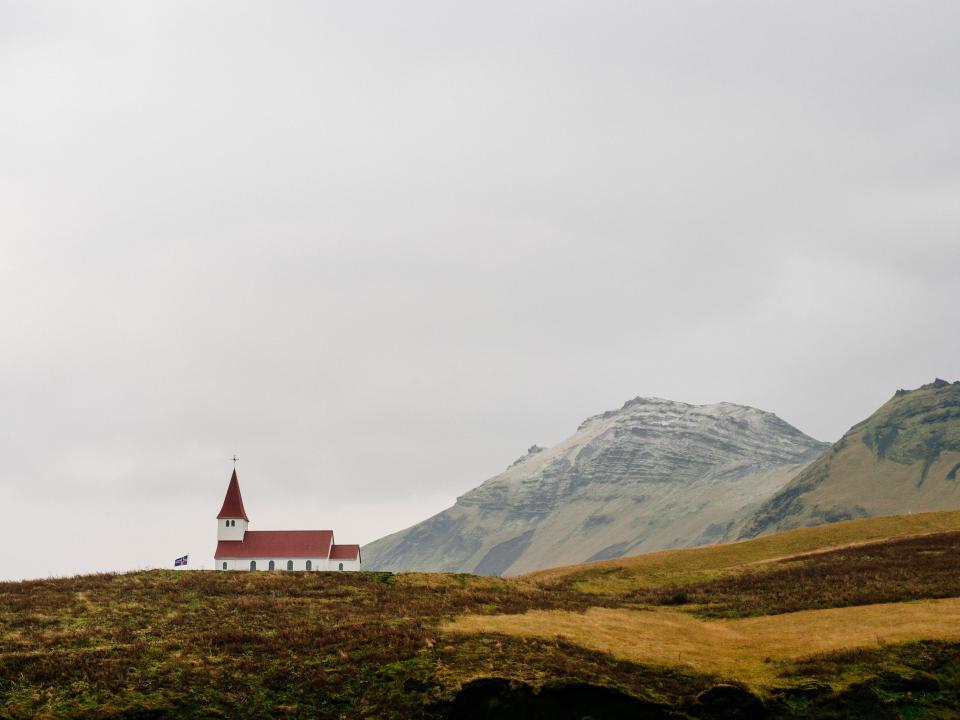 church, cross, red, roof, grey, sky, mountains, cliffs, hills, fields, valleys, grass, dirt, outdoors, plains, flag