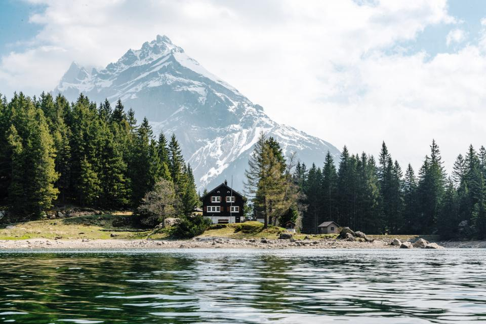 nature, landscape, mountains, summit, peaks, snow, forest, trees, shore, sand, rocks, grass, water, lake, ripples, surface, house, cottage, cabin, sky clouds