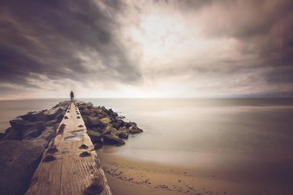 dock, pier, rocks, coast, shore, beach, sand, ocean, sea, sky, sunlight, clouds, cloudy, grey, nature, landscape