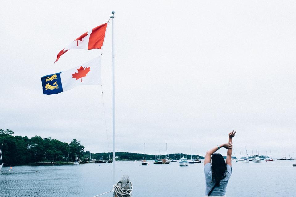 Canada, flags, girl, woman, marina, harbour, harbor, boats, lake, water, sky