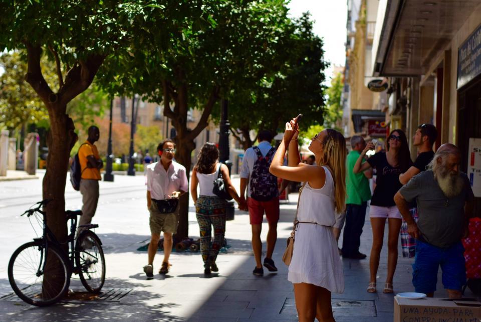girl, picture, seville, street, phone, sun, people, sidewalk, city