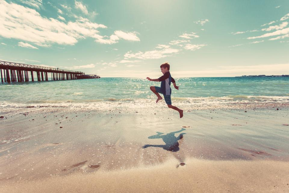 boy, beach, sand, shore, water, waves, ocean, sea, pier, sunshine, sunny, summer, sky, clouds, people, fun, jumping, people, child