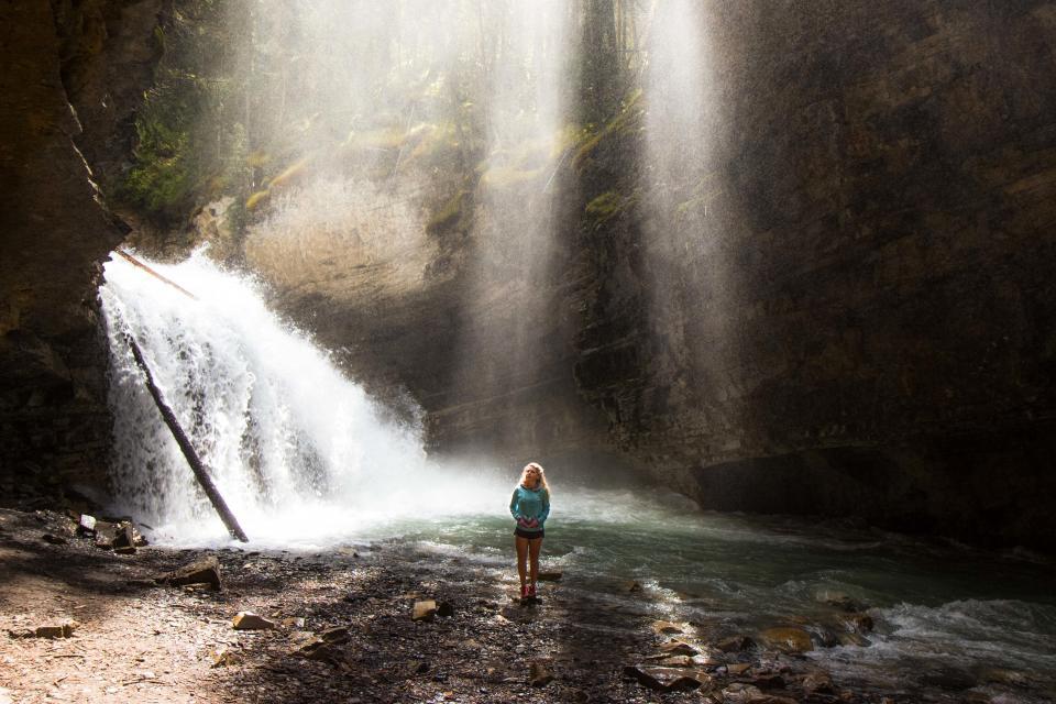 woman, girl, lady, people, stand, nature, water, waterfalls, lake, stream, splash, cave, rocks, vegetation, sunlight, sun, rays