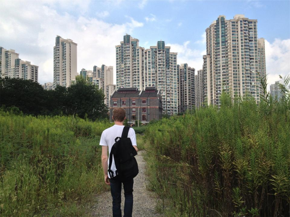 young, guy, student, walking, tshirt, backpack, trail, path, buildings, towers, condos, apartments, city, urban