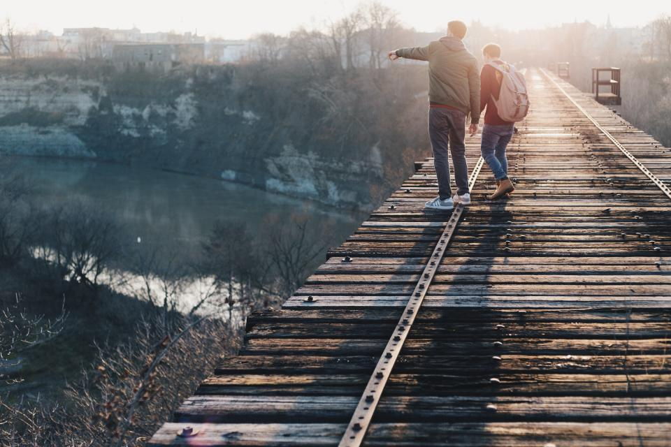 wood, bridge, people, looking, pointing, outdoors, nature, sunset, sunlight, sunshine, guy, man, guys, men, backpack, knapsack, lifestyle