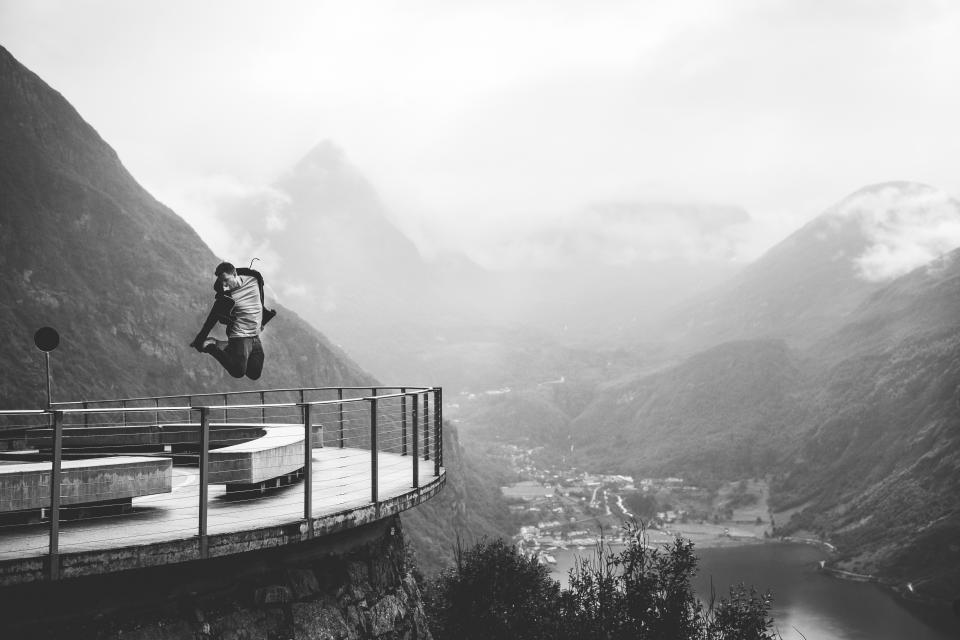 guy, man, jumping, lookout, railing, view, people, lifestyle, mountains, hills, cliffs, landscape, nature, river, clouds, black and white
