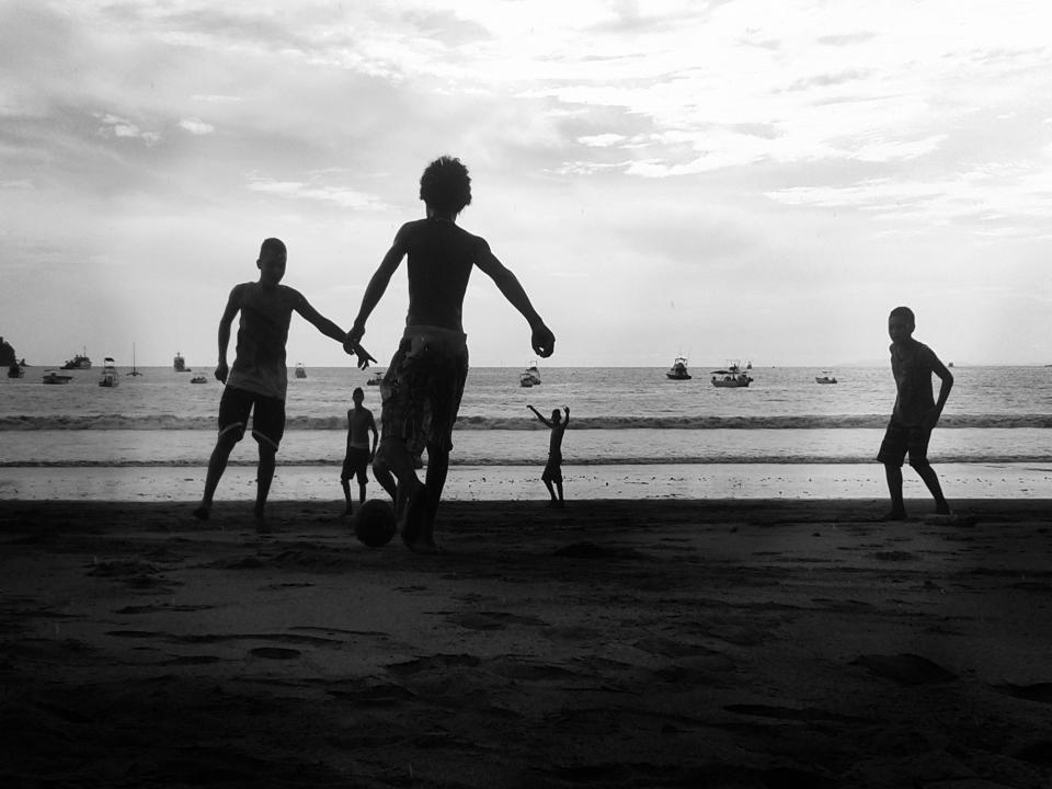 kids, children, playing, soccer, ball, beach, sand, shore, ocean, sea, water, boats, black and white