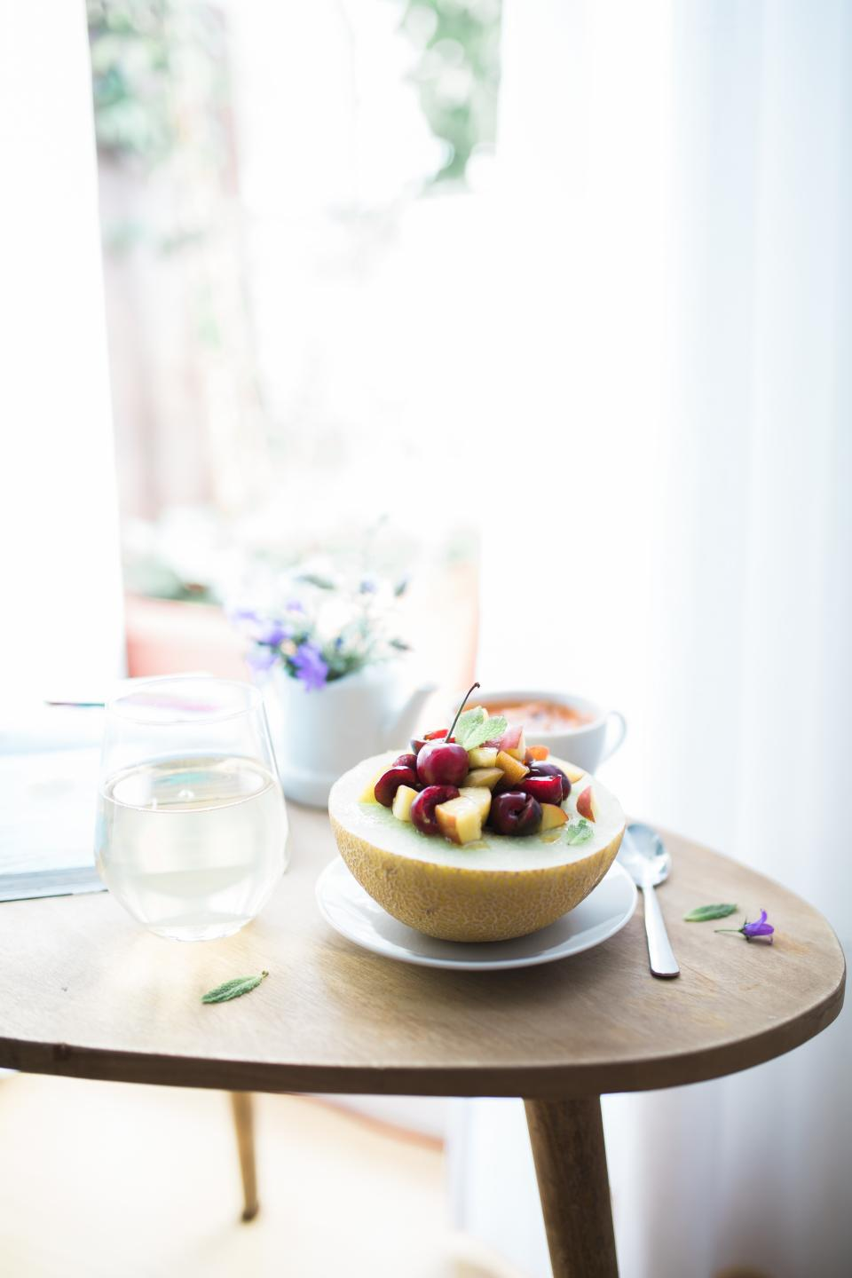 food, eat, gourmet, sliced, diced, fruits, vegetables, garnish, melon, honeydew, bowl, table, spread, plates, cups, flowers, teapot, curtains, white