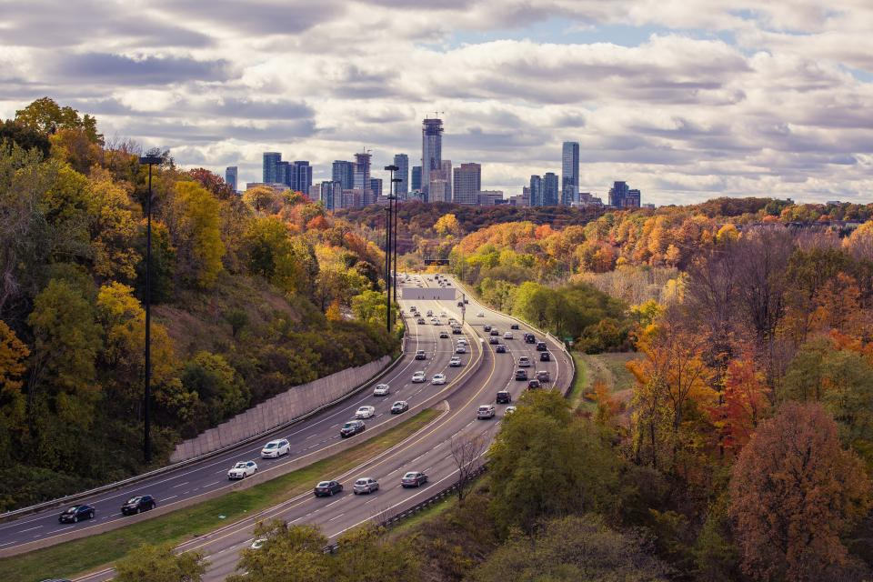 roads, highway, cars, traffic, city, urban, buildings, towers, high rises, sky, clouds, trees, fall, autumn
