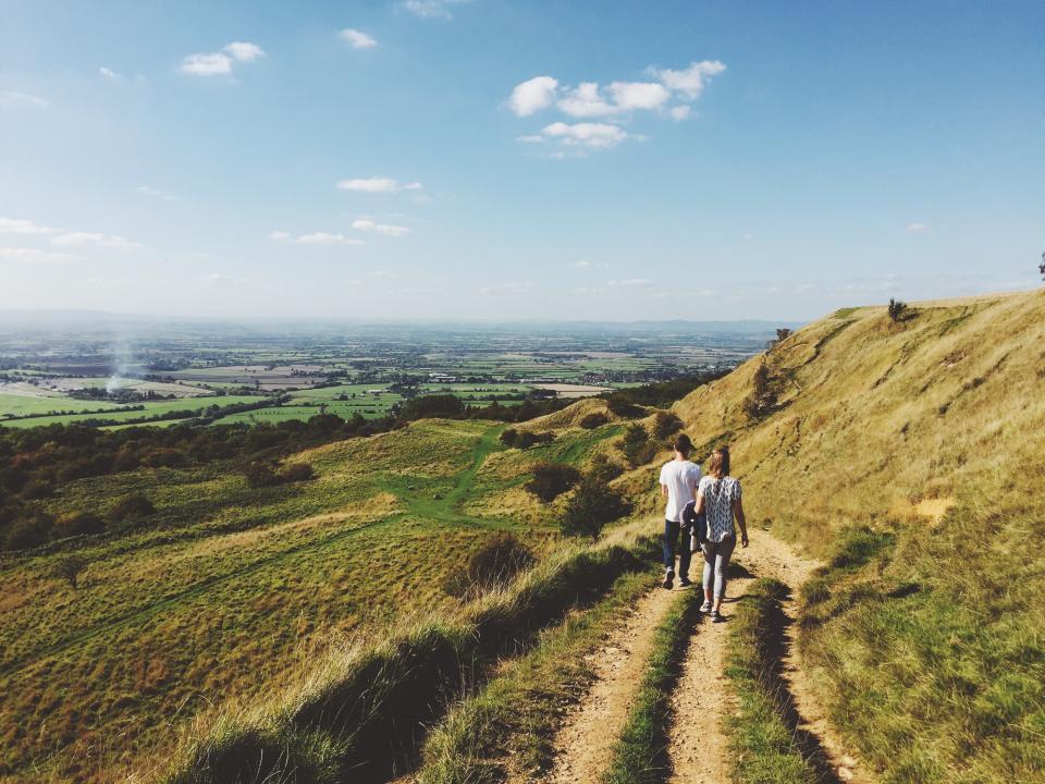 hiking, trekking, walking, people, girl, guy, green, grass, mountains, hills, landscape, nature, sunshine, blue, sky, summer, adventure, fields