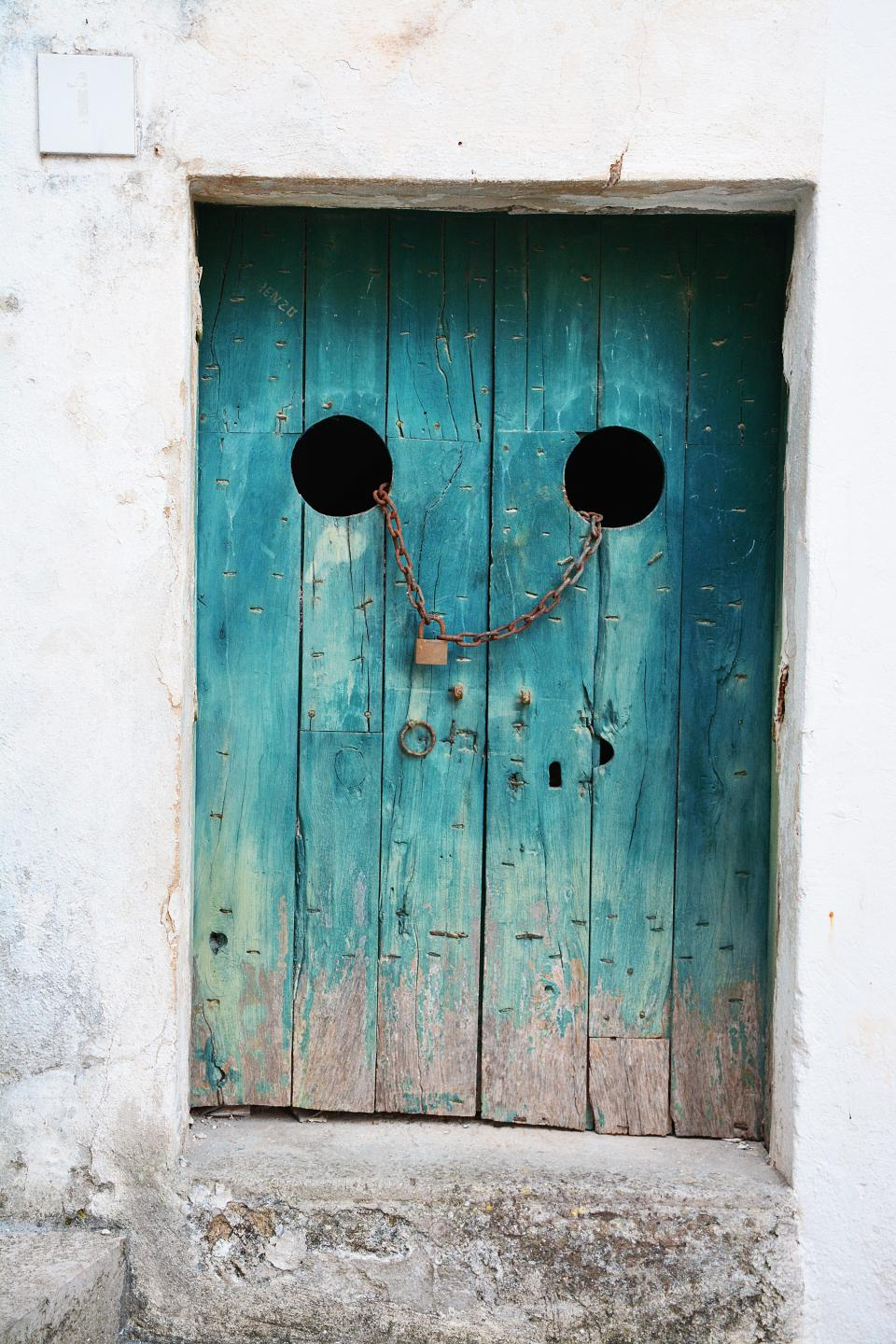 still, items, things, door, wood, panels, vertical, old, decrepit, holes, chains, lock, square, rectangles, teal, brown, rugged, grunge, minimalist