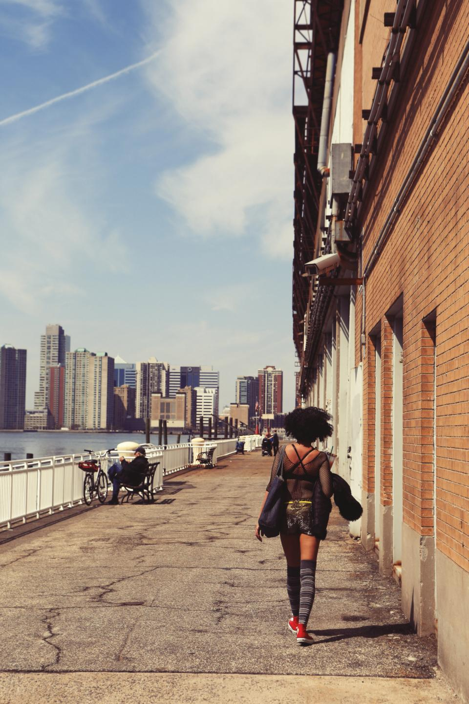 people, pedestrian, girl, woman, african american, fashion, socks, pedestrian, sidewalk, concrete, bench, railing, river, city, urban, buildings, architecture, sunny