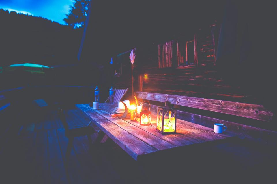 picnic table, deck, backyard, outdoors, night, dark, lanterns, lights, house, cottage, cabin