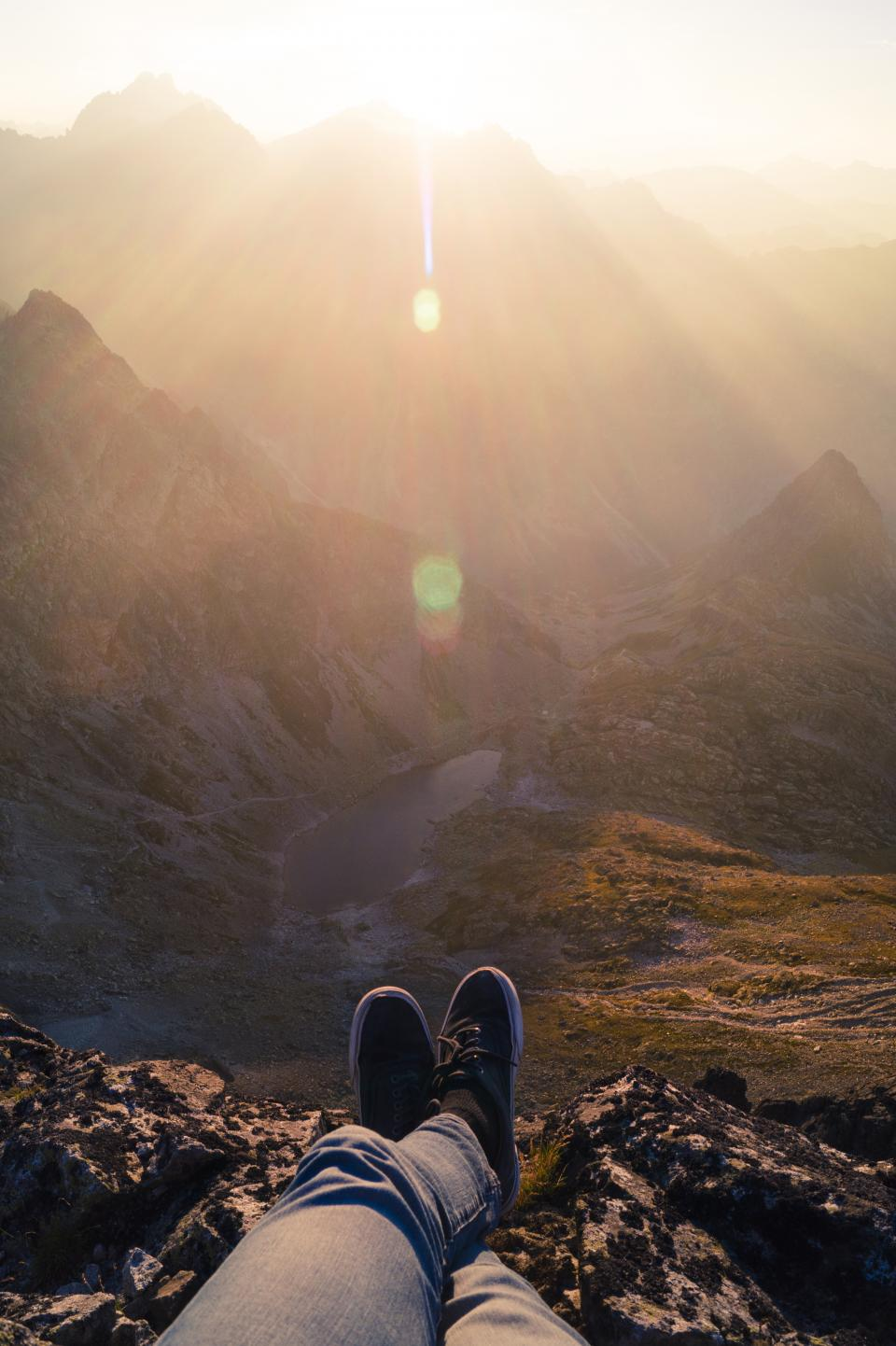 guy, man, male, people, feet, legs, shoes, sneakers, pants, nature, landscape, mountains, rocks, lake, sky, solar, flare, sunlight
