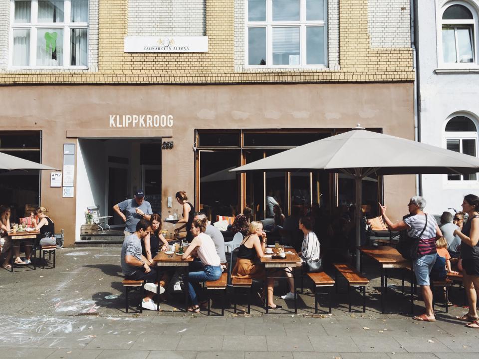people, guys, girls, friends, family, eat, drink, food, restaurant, outside, talking, wall, building, shade, sunlight, sunshine